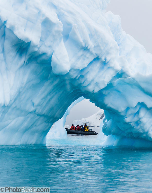 """A Zodiac boat explores a blue iceberg arch melting in Neko Harbor (an inlet of the Southern Ocean), at Graham Land, the north portion of the Antarctic Peninsula, Antarctica. Scientists have measured temperatures on the Antarctic Peninsula as warming faster than anywhere else on  earth. An overwhelming consensus of world scientists agree that global warming is indeed happening and humans are contributing to it through emission of greenhouse gases, primarily carbon dioxide (see www.ucsusa.org). Since the industrial revolution began, humans have increased atmospheric CO2 concentration by 35% (through burning of fossil fuels, deforesting land, and grazing livestock). Published in """"Light Travel: Photography on the Go"""" book by Tom Dempsey 2009, 2010. Published in Wilderness Travel Catalog of Adventures 2009, 2011."""