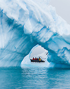 "A Zodiac boat explores a blue iceberg arch melting in Neko Harbor (an inlet of the Southern Ocean), at Graham Land, the north portion of the Antarctic Peninsula, Antarctica. Scientists have measured temperatures on the Antarctic Peninsula as warming faster than anywhere else on  earth. An overwhelming consensus of world scientists agree that global warming is indeed happening and humans are contributing to it through emission of greenhouse gases, primarily carbon dioxide (see www.ucsusa.org). Since the industrial revolution began, humans have increased atmospheric CO2 concentration by 35% (through burning of fossil fuels, deforesting land, and grazing livestock). Published in ""Light Travel: Photography on the Go"" book by Tom Dempsey 2009, 2010. Published in Wilderness Travel Catalog of Adventures 2009, 2011."