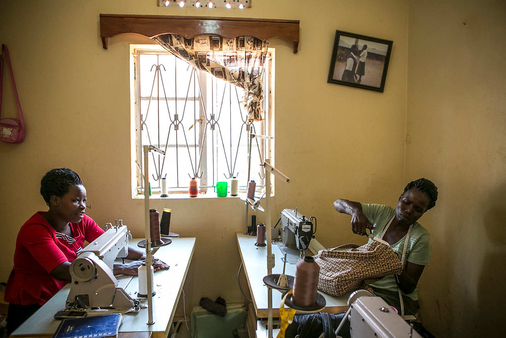 Akot Vicky, at right, 34, a former girl soldier and sex slave, works on her bag inside an NGO, WEND Africa, in Gulu. Vicky was abducted when she was 12 years old in Lamwo District and was assigned to a captain and started a one-month military training the next day. The captain's first wife ran away, so she was the only wife for him at that time. But he had 14 wives by the time she escaped after staying in the bush for nine years. She gave birth to two girls in the bush and escaped with them while eating the ants' hill on the ground.