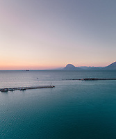 Aerial view of fishing boat on horizon at sunset from marina in Patras, Greece