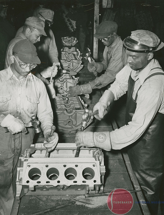 Studebaker Foundry workers remove casting flash from V8 cylinder blocks.