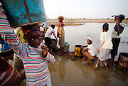 Girls fill containers with water at the Dikunani dam in Savelugu, northern Ghana, on Friday March 9, 2007. The only of four water sources that has not completely dried out around Savelugu, the pond is used by hundreds of people daily who sometimes walk several kilometers to fetch water. Despite the presence of mesh filters available to people who come get water, cases of guinea worm in the area have gone up sharply in the recent months.
