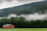 Cornwall, New York - A view of flog and clouds over Clove Brook Farm with Schunnemunk Mountain in the background on the morning of Aug. 14, 2018.