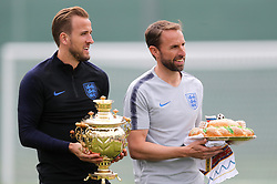 England's Harry Kane (left) and manager Gareth Southgate receive a Russian samovar - a heated metal container traditionally used to heat and boil water, and a karavai - a large round loaf of bread, both symbolizing hospitality during the training session at the Spartak Zelenogorsk Stadium, Repino.