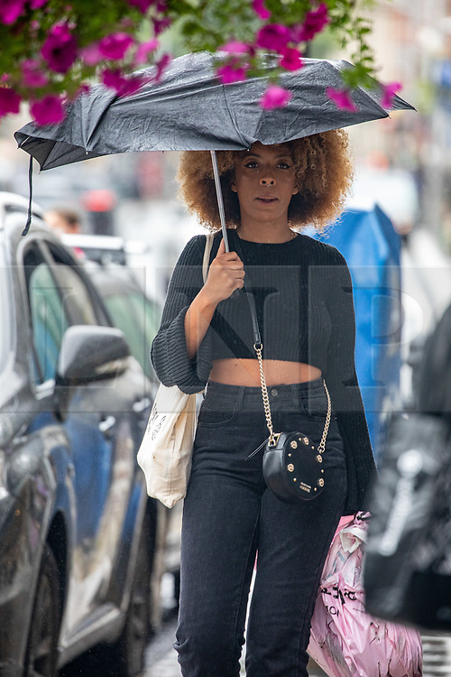 © Licensed to London News Pictures. 19/08/2020. London, UK. A shoppers on the Kings Road gets caught in heavy rain and gusty winds in Kensington in South West London today as storm Ellen hits the UK. Weather forecasters have predicted torrential rain and high winds before a warmer front develops this week with sunnier weather and highs of 24c. Photo credit: Alex Lentati/LNP
