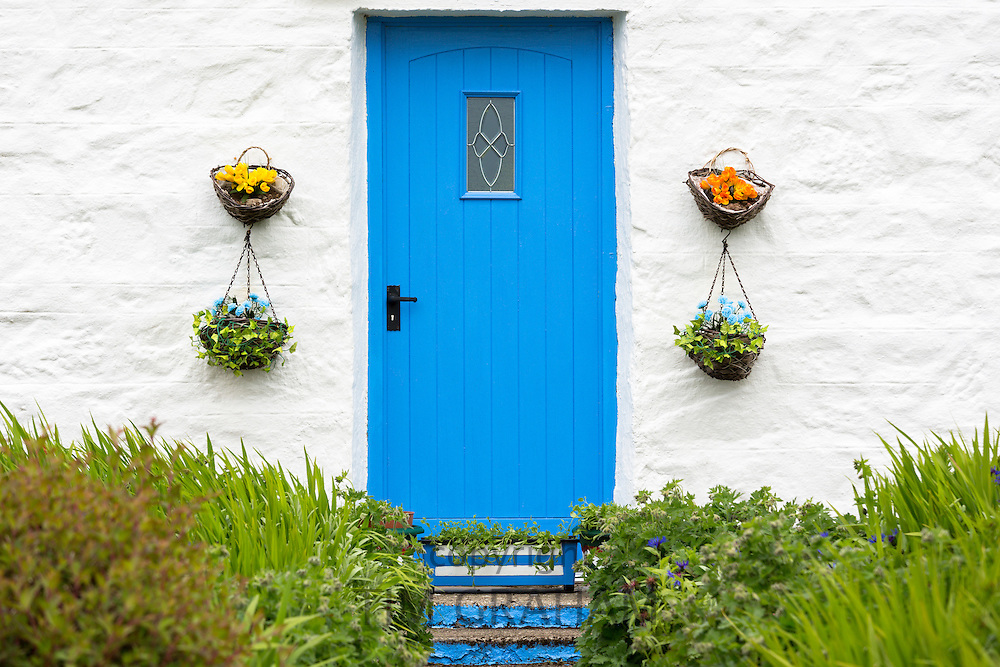 Traditional cottage wooden front door with hanging flower baskets and front garden on Isle of Skye, the Western Isles of Scotland, UK