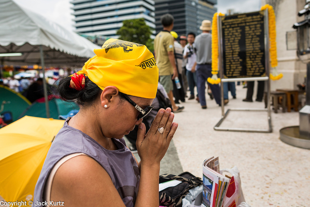 04 AUGUST 2013 - BANGKOK, THAILAND: A woman prays at a shrine to the Thai monarchy during a pro-monarchy/anti-government rally in Bangkok. About 2,000 people, members of the  People's Army against Thaksin Regime, a new anti-government group, protested in Lumpini Park in central Bangkok. The protest was peaceful but more militant protests are expected later in the week when the Parliament is expected to debate an amnesty bill which could allow Thaksin Shinawatra, the exiled former Prime Minister, to return to Thailand.     PHOTO BY JACK KURTZ