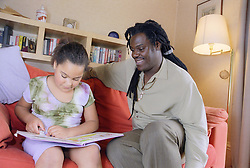 Single father sitting on sofa reading story book with young daughter,