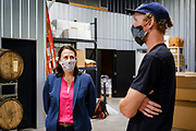 """22 JULY 2020 - AMES, IOWA: THERESA GREENFIELD, left, and ELLIOT THOMPSON, owner of Alluvial Brewing, talk about the needs of small businesses during a visit by Greenfield to Alluvial Brewing in Ames, IA. Greenfield, a Democrat, is running for the US Senate against incumbent Republican Senator Joni Ernst. Recent polls have Greenfield slightly ahead of or statistically tied with Ernst, who is closely allied with President Donald Trump. Although Greenfield is not doing much in person campaigning with big events, she is meeting with business people across the state of Iowa to promote her """"Small Towns, Bigger Paychecks"""" economic program.        PHOTO BY JACK KURTZ"""