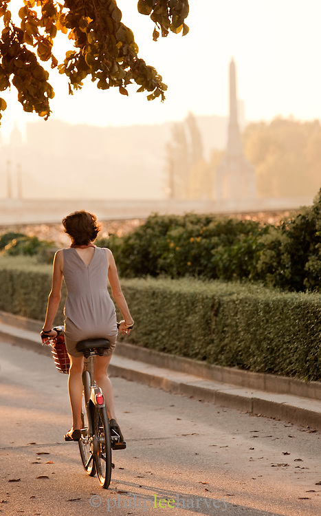A woman cycles near the Notre Dame de Paris cathedral in the early morning in Paris, France