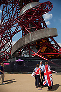 London, UK. Thursday 9th August 2012. London 2012 Olympic Games Park in Stratford. People pass the base of the Orbit art sculpture by Anish Kapoor.