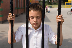 Boy looking through the fence out of the school playground,