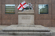 While a shrine of flowers and messages continue to grow ten days after the terrorist attack on London Bridge and Borough Market, the Griffin marking the southern-most boundary of the City of London - the capitals financial district - has been draped with the English flag aka the Cross of St. George, on 12th June 2017 in London, England. Near the southern-most boundary of the City of London, where tLondoners and visitors to the capital leave their emotional and defiant poems and personal messages on post-it notes.