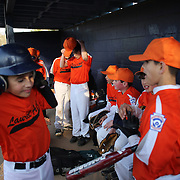 Young baseball players warming up in the dugout during the Norwalk Little League baseball competition at Broad River Fields,  Norwalk, Connecticut. USA. Photo Tim Clayton