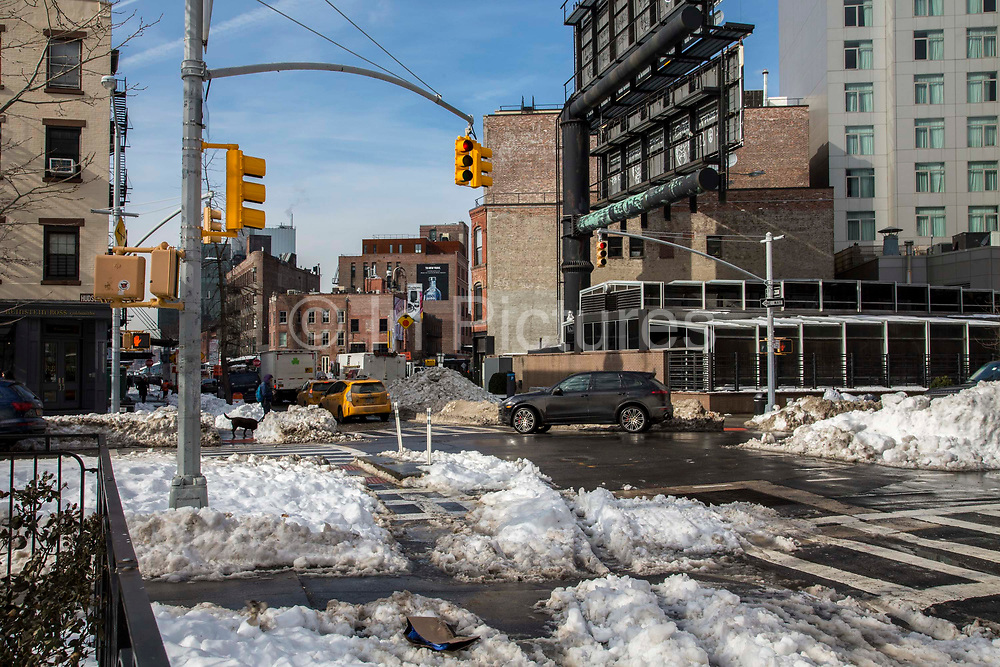 A black car drives and follows yellow taxis through a street intersection of Husdon Street and Gansevoort Street, New York City, New York, United States of America. The streets have mounds of snow on the side where they have been cleared after the record breaking snowstorm in January 2016.