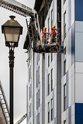 """© Licensed to London News Pictures. 16/11/2019. Bolton, UK. Firefighters work at the scene where a fire broke out overnight (15th/16th November 2019) at a block of flats known as """" The Cube """" , in Bolton Town Centre . At least two people are known to have been treated by paramedics at the scene of the six-story block , which is occupied by students of the University of Bolton . Photo credit: Joel Goodman/LNP"""
