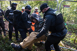 National Eviction Team bailiffs working on behalf of HS2 Ltd forcibly move an anti-HS2 activist away from a fence being constructed during evictions from a wildlife protection camp in the ancient woodland which inspired Roald Dahl's Fantastic Mr Fox at Jones' Hill Wood on 1 October 2020 in Aylesbury Vale, United Kingdom. Around 40 environmental activists and local residents, some of whom living in makeshift tree houses 60 feet above the ground, were present during the evictions at Jones' Hill Wood which had served as one of several protest camps set up along the route of the £106bn HS2 high-speed rail link in order to resist the controversial infrastructure project.
