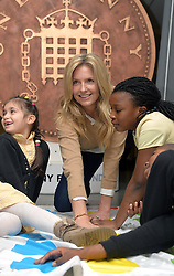 Image ©Licensed to i-Images Picture Agency. 18/12/2014. London, United Kingdom. <br /> <br /> Penny Lancaster visits Charlton Manor Primary School where the Mayors Fund initiative 'Penny for London' is raising money to fund breakfasts for school children.<br /> <br /> Penny Lancaster plays twister during breakfast club.<br /> <br /> Picture by Ben Stevens / i-Images