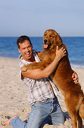 man on the beach with a dog jumping up on him.
