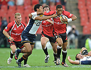Right Wing of the Lions, Ashwin Willemse is tackled by left wing of the Brumbies, Francis Fainifo with Cobus grobbelaar and Jano Vermaak in support in the Super 14 match between the Lions and the Brumbies that took place on Saturday 21 March 2009 at Coca-Cola Park in Johannesburg South Africa. The Lions won this Super 14 match against the Brumbies 25 - 17.  <br /> Photographer : Anton de Villiers / SASPA