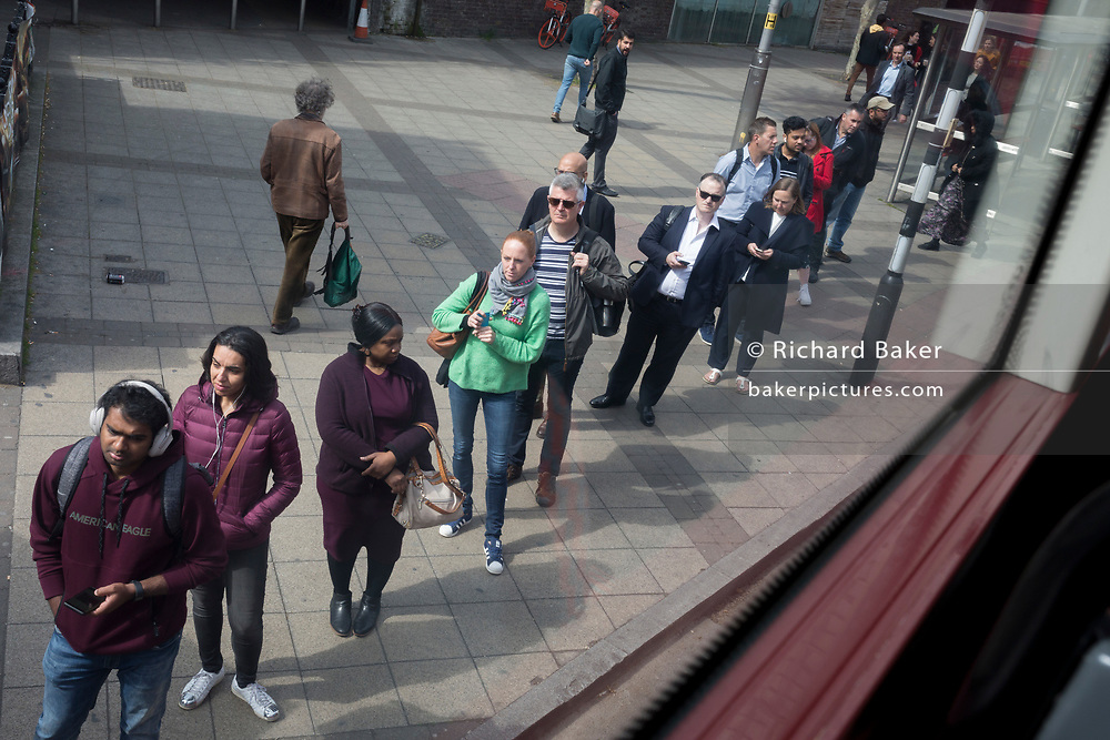 Bus passengers queue for their next service near Waterloo station, on 7th May 2019, in London, England.