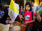 19 NOVEMBER 2017 - HWAMBI, YANGON REGION, MYANMAR: A girl with a papal flag she bought at Sacred Heart's Catholic Church in Hwambi, about 90 minutes north of Yangon. Catholics in Myanmar are preparing for the visit of Pope Francis. He is coming to the Buddhist majority country November 27-30. There about 500,000 Catholics in Myanmar, about 1% of the population. Catholicism was originally brought to what is now Myanmar more than 500 years ago by Portuguese missionaries and traders.    PHOTO BY JACK KURTZ