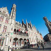 A wide-angle shot of buildings in the Markt (Market Square) in the historic center of Bruges, a UNESCO World Heritage site.