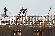 Wawayanda, New York - Men work on the roof of a three-story building under construction on March 3, 2016.  The structure is being built by Nowak Properties Inc., and will be a 108-room Sleep Inn hotel.