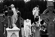 Onlookers trying to get the best vantage point in Glasnevin cemetery to view the burial  of Eamon de Valera.<br /> 31/08/1975