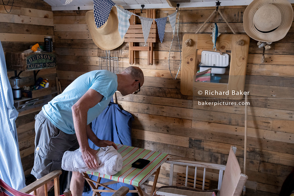 An interior of a seaside resort beach hut, property owned by friends of a man who is tidying the interior, after an afternoon spent swimming and resting, on 25th July 2021, in Whitstable, Kent, England.
