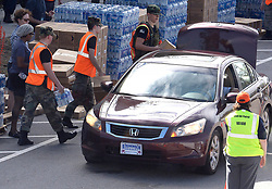 Volunteers carry free supplies to waiting motorists Tuesday, September 18, 2018 in downtown Wilmington, N.C. as New Hanover County, in partnership with FEMA, the Civil Air Patrol and volunteers from General Electric, gave out free water, tarps and the Meals Ready to Eat to county residents at three different locations in Wilmington. Photo by Chuck Liddy/Raleigh News & Observer/TNS/ABACAPRESS.COM
