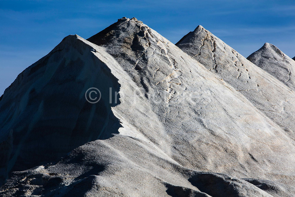 A landscape of sea salt mountains extracted from salt pans, on 19th October 2016, in Gruissan, France. The traditional industry around Gruissan is salt making - it is the residue of evaporated sea water. The salt from Saint Martins saltern is the result of a salt marsh technique, which dates back to Antiquity. You can see the fields of salt water and piles of brown and white salt - called camelles because of their resemblance to the humps of camels. Salt pans cover a total surface area of almost 400 hectares between the sea and the island of St Martin. The harvest has grown from around 5 tons in 1912, to more than 30,000 tons today, in a good year. Water from the sea is pumped into the salt pans in spring. It evaporates during the summer, and salt is harvested in autumn.  The salt, much prized, is called Fleur de sel.