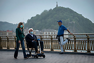 A couple, wearing protective face masks, strolls along the Zurriola promenade. Donostia (Basque Country). May 7, 2020. Some outdoor activities have been allowed as Spain is going through the plan of downscaling following an ongoing plan to leave the confinement ordered by the Spanish government to prevent the spread of the COVID-19. (Gari Garaialde / Bostok Photo)