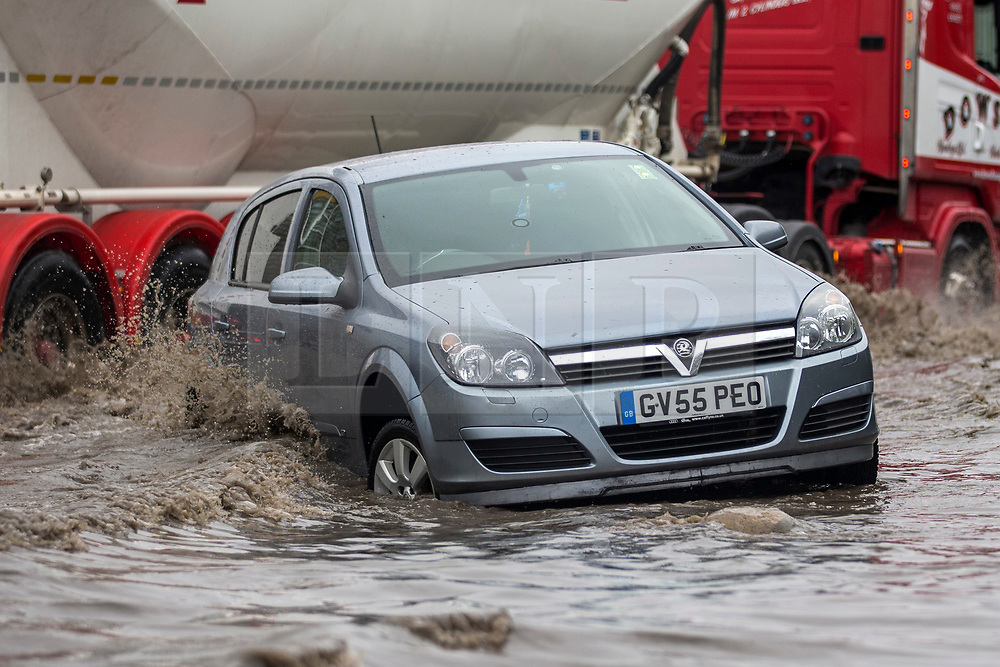 © Licensed to London News Pictures. 06/03/2019. Leeds UK. A  lorry drives through flood water passing an abandoned car in Leeds this morning. Heavy rain last night has caused flooding in Leeds this morning leaving cars abandoned in flood water on Knowsthorpe Lane in the Cross Green area of the city. Photo credit: Andrew McCaren/LNP