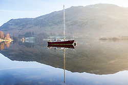 © Licensed to London News Pictures. 21/02/2018. Glenridding UK. A boat reflects into the calm water of Ullswater lake this morning on a sunny day in Cumbria. Photo credit: Andrew McCaren/LNP