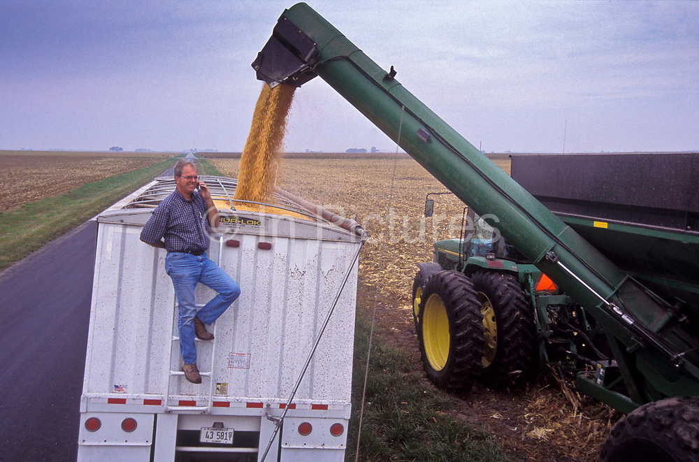 A farmer taking on a mobile phone as he oversees the loading of Corn in America's Corn belt of Illinois state, USA.