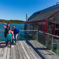 Old fish processing buildings are now a fishing museum in Lubec, Maine. High tide. Lubec Narrows.