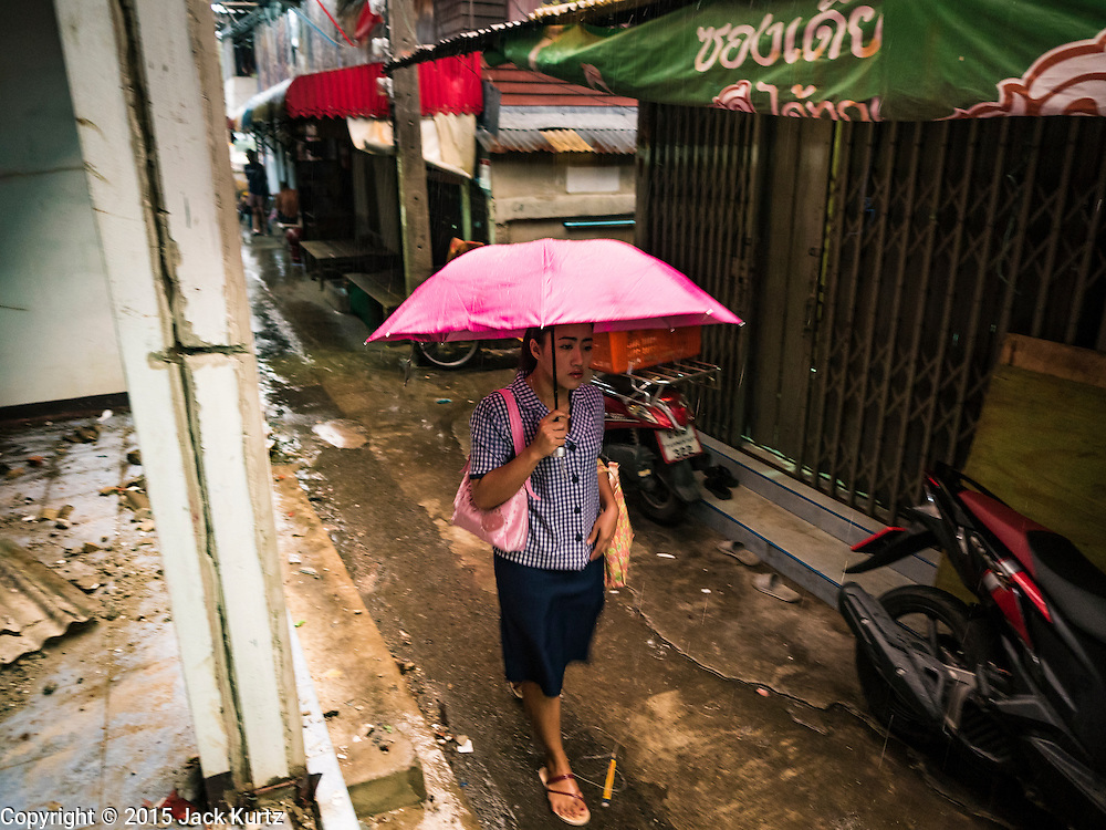 28 SEPTEMBER 2015 - BANGKOK, THAILAND: A woman walks past an abandoned and condemned home near Wat Kalayanamit. Fifty-four homes around Wat Kalayanamit, a historic Buddhist temple on the Chao Phraya River in the Thonburi section of Bangkok, are being razed and the residents evicted to make way for new development at the temple. The abbot of the temple said he was evicting the residents, who have lived on the temple grounds for generations, because their homes are unsafe and because he wants to improve the temple grounds. The evictions are a part of a Bangkok trend, especially along the Chao Phraya River and BTS light rail lines. Low income people are being evicted from their long time homes to make way for urban renewal.    PHOTO BY JACK KURTZ