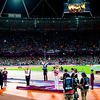 British hepthathalon athlete Jessica Ennis leaps onto the podium to receive her gold medal along with silver medalist Jessica Zelinka and bronze medalist Brianne Theisen during the 2012 London Summer Olympics.