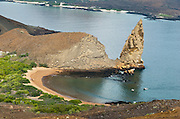 Pinnacle Rock on Bartolomé Island is an icon of the Galápagos archipelago. This large black partially eroded lava formation was created when volcanic magma reached the sea and exploded into particles which fastened together into rock comprised of thin layers. Bartolomé Island (or Bartholomew Island, named after Lieutenant David Bartholomew of the British Navy) is one of the geologically younger islands in the Galápagos archipelago, just off the east coast of Santiago (James) Island. The volcanic Galápagos Islands (officially Archipiélago de Colón, otherwise called Islas de Colón, Islas Galápagos, or Enchanted Islands) are distributed along the equator in the Pacific Ocean 972 km west of continental Ecuador, South America. In 1959, Ecuador declared 97% of the land area of the Galápagos Islands to be Galápagos National Park, which UNESCO registered as a World Heritage Site in 1978. Ecuador created the Galápagos Marine Reserve in 1998, which UNESCO appended in 2001.