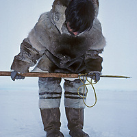 An Inuit hunter waits by a seal breathing hole north of Baffin Island, Nunavut, Canada.