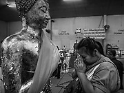31 MAY 2017 - CHACHOENGSAO, THAILAND:  Women pray at a statue of the Buddha at Wat Sothon (also spelled Sothorn) in Chachoengsao, Thailand. The temple is one of the largest and most visited in Thailand. People make merit by paying to wrap the Buddha statues in orange robes. The temple is most famous because people leave hard boiled eggs as an offering at the temple. They ask for business success or children and leave hundreds of hard boiled eggs.     PHOTO BY JACK KURTZ