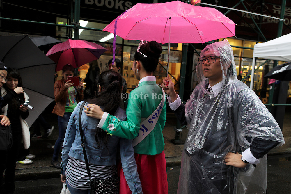 Miss Korea posing for images with the public while it is raining New York City in the Koreatown district