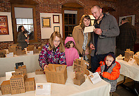 Grace Sorter finds her mill as Colvin Williams, Kerrie Sorter, Brian Lord and Brodee Lord read about the Mill replicas made by Elm Street School 3rd graders on display at the Belknap Mill Thursday evening.  (Karen Bobotas/for the Laconia Daily Sun)
