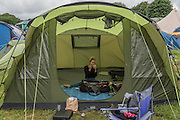 Preparing for the day in an empty tent as people get ready to enjoy the final day and also leave later - The 2016 Glastonbury Festival, Worthy Farm, Glastonbury.