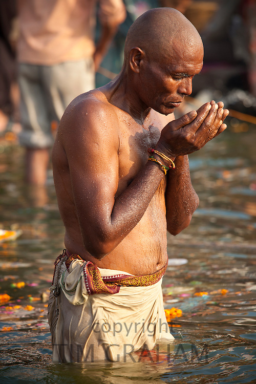 Indian Hindu pilgrims bathing in The Ganges River at Dashashwamedh Ghat in Holy City of Varanasi, Benares, India RESERVED USE - NOT FOR DOWNLOAD -  FOR USE CONTACT TIM GRAHAM