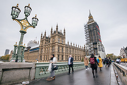 © Licensed to London News Pictures. 09/11/2017. London, UK. Pedestrians cross Westminster Bridge as Big Ben chimes at 9am. The bell has been silenced since August 21 during repairs to the Elizabeth Tower. Palace of Westminster clockmakers will work through the day adjusting the bells to ensure that they strike at exactly the right time for Armistice Day commemorations at the 11th hour of November 11, followed by Remembrance Sunday events the following day. Photo credit: Rob Pinney/LNP