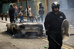 © Licensed to London News Pictures . 08/08/2011 . London , UK . Police in Hackney guarding a burned out car on a 3rd night of rioting and looting in London , which followed a protest against the police shooting of Mark Duggan in Tottenham . Photo credit : Joel Goodman/LNP
