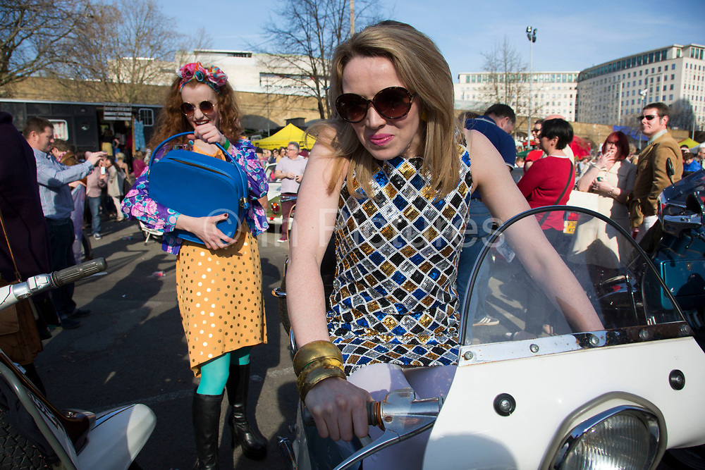 The Classic Car Boot Sale at the Southbank Centre, South Bank, London, UK. Vintage cars, fashion and style assemble together to celebrate all things classic from the 1940s to 1960s. Girls in 60s clothes larking around dancing and generally causing mischief.