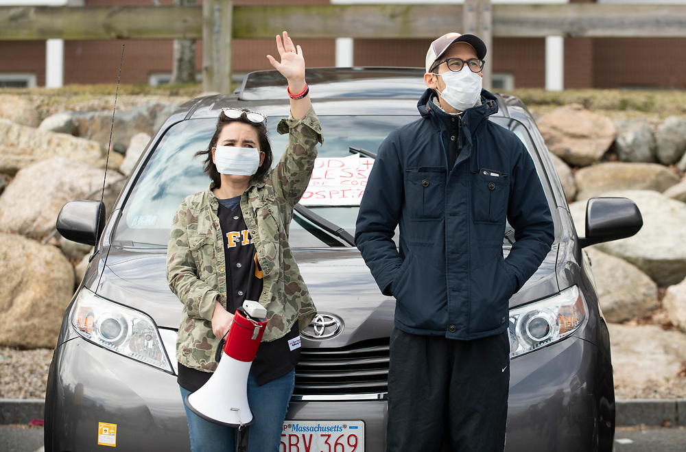 HYANNIS - Organizer Inna Taylor, youth director at Grace Church and her husband Andrew Taylor wave to healthcare works from the Cape Cod Hospital parking lot on Friday, April 10, 2020.
